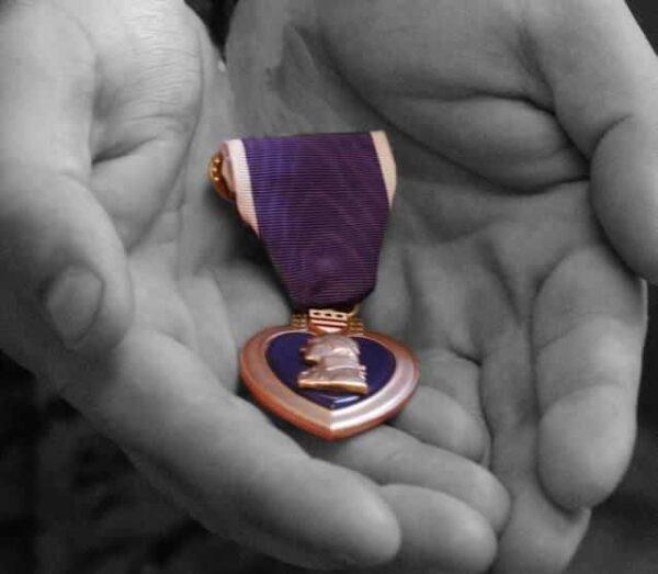 Hands holding a Purple Heart