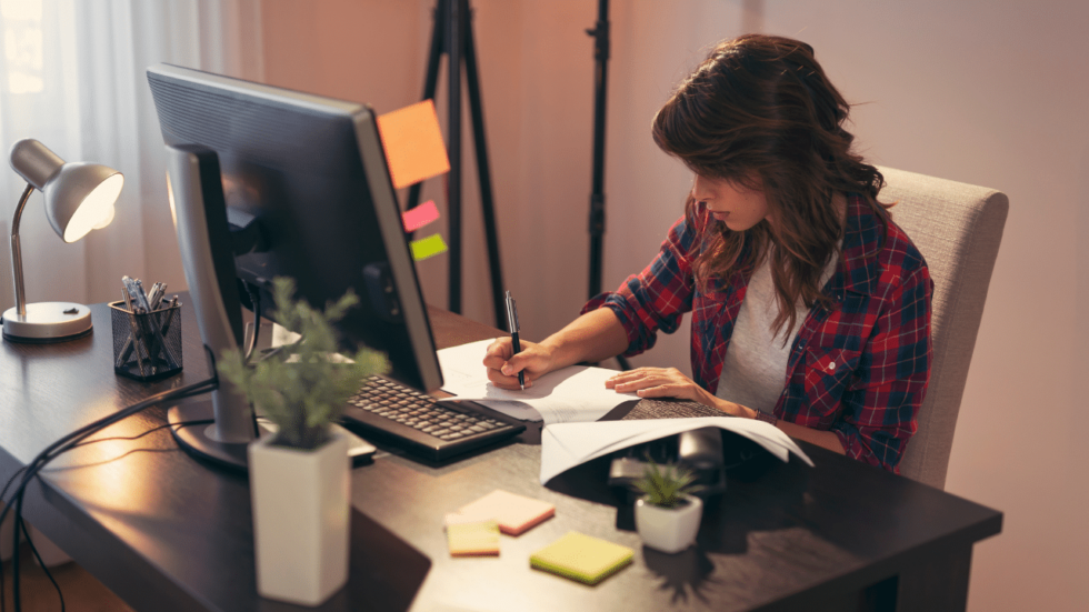 Woman sitting at home office desk writing on a piece of paper