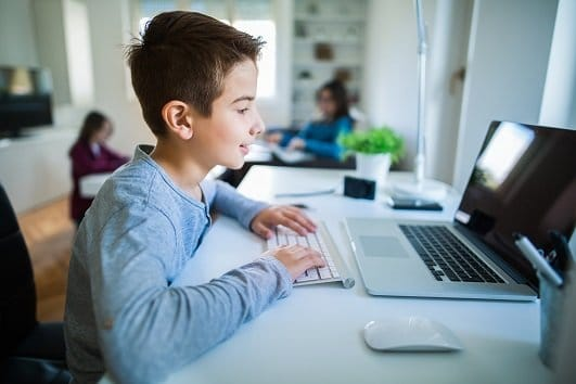 school boy at home with computer