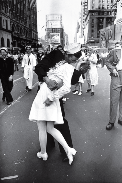 In New York's Times Square a white-clad girl clutches her purse and skirt as an uninhibited sailor plants his lips squarely on hers