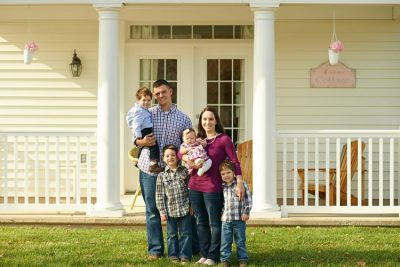 Military family standing in front of their home