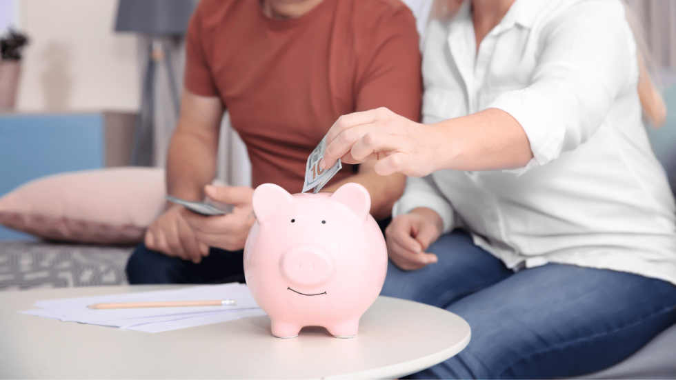 Couple putting money in a piggy bank