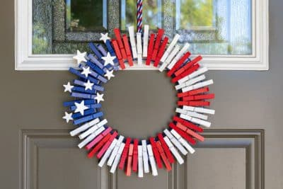 Front door wreath made out of clothespins and decorated to look like an American flag for Independence Day