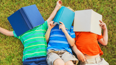 Three children laying in the grass with books