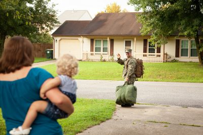 Servicemember waving goodbye to his family as he leaves for deployment